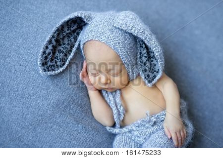 lovely newborn boy in blue hare suit with long ears
