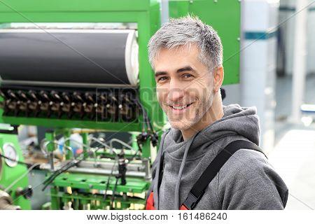 Auto mechanic workshop. Car mechanics. Auto mechanic checks the operation of the fuel injection.