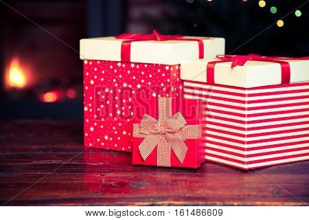 festive red Gift Boxes standing by the Burning Fireplace and Christmas tree - cozy home