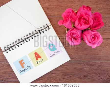 Word spell FAQ and handwriting frequently asked questions on notebook and pink rose flower with wood background on top view
