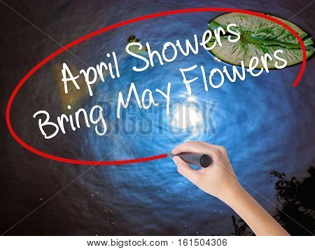 Woman Hand Writing April Showers Bring May Flowers With Marker Over Transparent Board