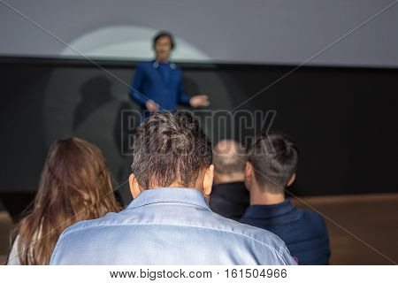 Spokesperson Speaks To An Audience At A Business Conference. Free Copy Space For Your Vertical Inscr