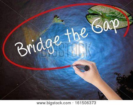 Woman Hand Writing Bridge The Gap With Marker Over Transparent Board