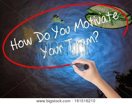 Woman Hand Writing How Do You Motivate Your Team? With Marker Over Transparent Board