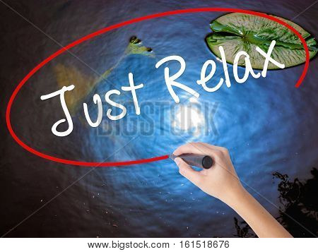 Woman Hand Writing Just Relax With Marker Over Transparent Board