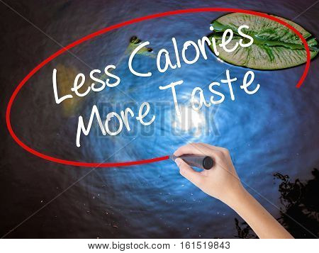 Woman Hand Writing Less Calories More Taste With Marker Over Transparent Board