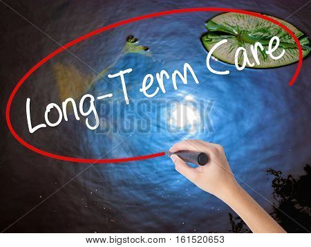 Woman Hand Writing Long-term Care With Marker Over Transparent Board