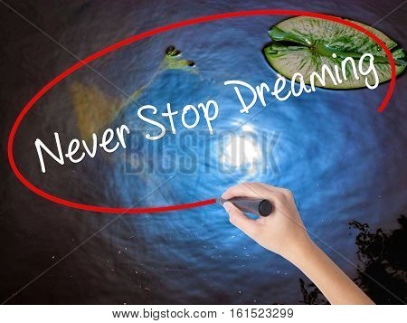 Woman Hand Writing Never Stop Dreaming With Marker Over Transparent Board
