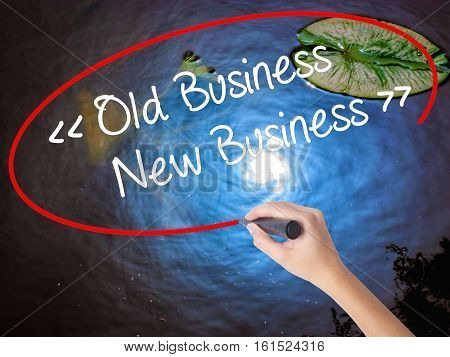 Woman Hand Writing Old Business - New Business With Marker Over Transparent Board