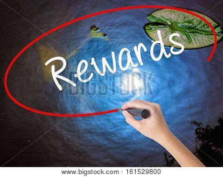 Woman Hand Writing Rewards With Marker Over Transparent Board