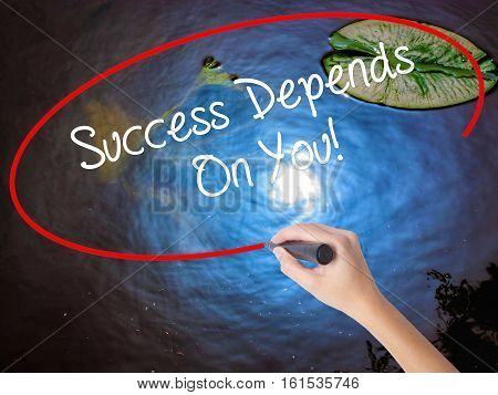 Woman Hand Writing Success Depends On You! With Marker Over Transparent Board