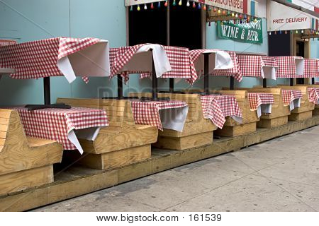 Wooden Benches And Stacked Tables In Little Italy