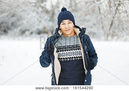 Handsome Guy In A Knitted Sweater With Patterns And A Winter Jacket Posing On A Snowy Day