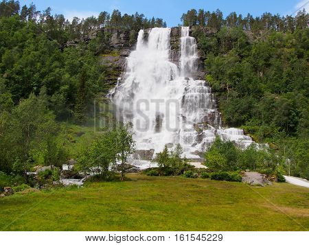 Norwegian waterfall sunny summer day Waterfall Tvindefossen Norway. Waterfall Tvindefossen is the largest and highest waterfall of Norway it is famous for its beauty