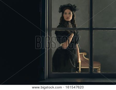 Vintage Victorian Woman In Black Dress Standing Behind Window With Candlelight.