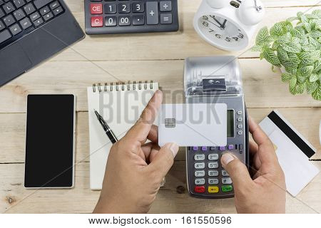 Hand Holding Credit Card Terminal Or Edc On Cashier Wooden Table In The Store With Calculator, Clock