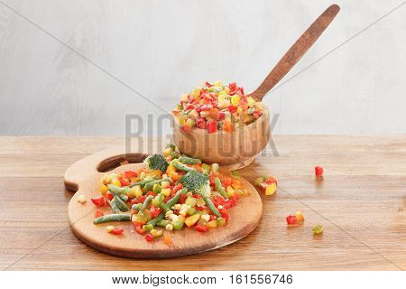 Healthy food frozen vegetables. Cooking ingredients on wooden cutting board.