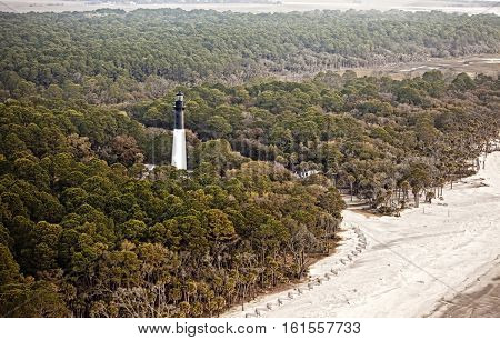 Hunting island lighthouse, built in 1859, on Hunting Island South Carolina, aerial view. The lighthouse is surrounded by maritime pine, live oak, and palmetto forest.