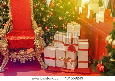 Christmas gifts presents boxes near luxurious red chair Santa Claus throne surrounded by multiple gift boxes