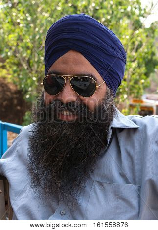 Chandigarh, India. 1 June 2009: Rural residents in daily life. Closeup portrait of a brave Sikh, a Rock garden, the second most visited tourist attraction in India after Taj Mahal. The foothills of the Himalayas, Northwest of India, Chandigarh, capital of