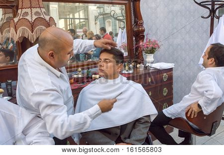 TBILISI, GEORGIA - SEP 25, 2016: Barber shaves a young man in a retro-style barbershop during the weekend on September 25, 2016. Tbilisi has population of 1.5 million people