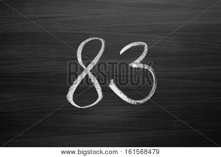 number eighty three enumeration written with a chalk on the blackboard