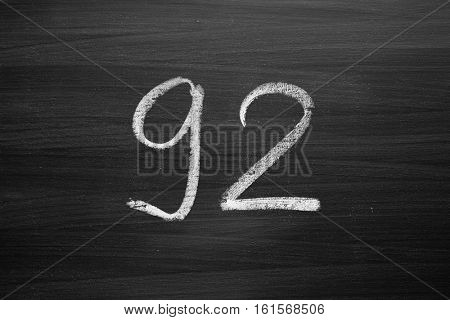 number ninety two enumeration written with a chalk on the blackboard