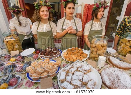 TBILISI, GEORGIA - SEP 25, 2016: Cute young girls selling cookies cakes and pies during a local street festival on the weekend on September 25, 2016. Tbilisi has population of 1.5 million people