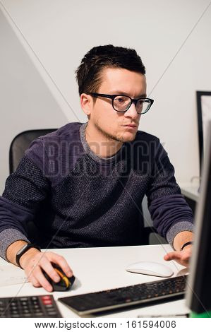 Busy working. Pensive young handsome man wearing glasses working on laptop while sitting at his working place.