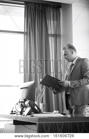 Side view of mature businessman reading file at desk in office