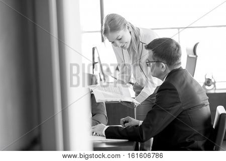 Young businesswoman showing book to businessman in meeting room