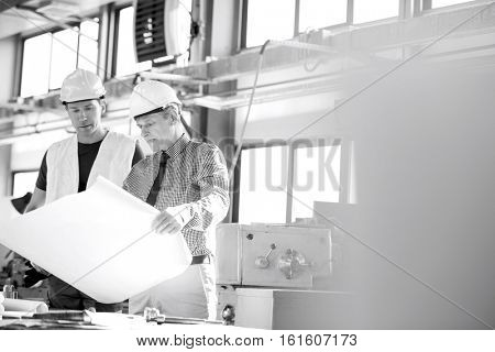 Male architect and manual worker examining blueprint in metal industry