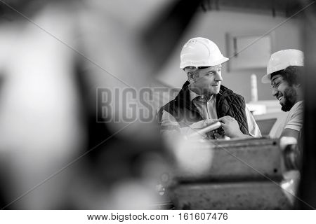 Mature male supervisor talking with worker in metal industry
