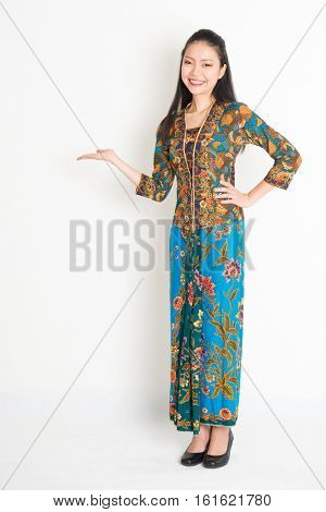 Portrait of young southeast Asian woman in traditional Malay batik kebaya dress smiling, full length standing on plain background.
