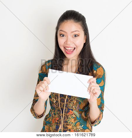 Portrait of young southeast Asian woman in traditional Malay batik kebaya dress hand holding a white blank paper card with surprised face expression, standing on plain background.