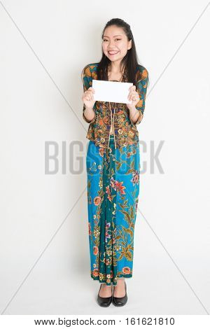 Portrait of young southeast Asian woman in traditional Malay batik kebaya dress hand holding a white blank paper card, full length standing on plain background.