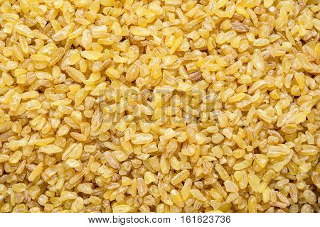 Bulgur grains, cracked wheat as a background. Macro shot of bulgur / bulghur