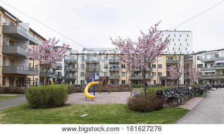UPPSALA, SWEDEN ON MAY 09. View of modern blocks of apartments and yard on May 09, 2013 in Uppsala, Sweden. Open playground in the middle, springtime. Unidentified people. Editorial use.
