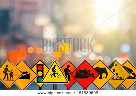 Set Of Traffic Warning Sign On Blur Traffic Road With Colorful Bokeh Light Abstract Background.