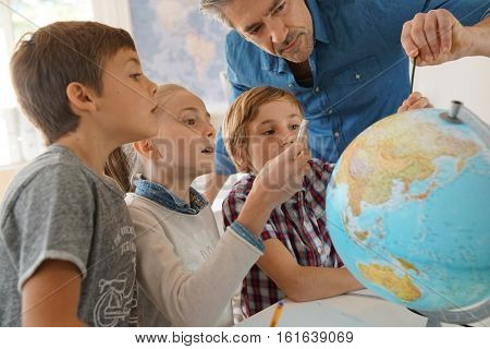 Teacher with kids in geography class looking at globe