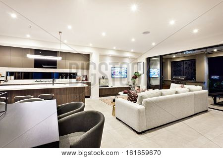 Modern living room with a television and sofas and pillows beside a dining area and kitchen there is an entrance to an outside patio area