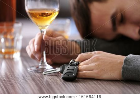 Drunk man sitting at table with car key and glass of alcoholic beverage, closeup. Don't drink and drive concept