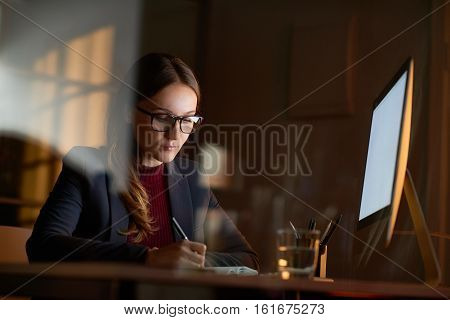 Portrait of young stylish woman wearing formal suit and glasses working alone in dark office late in the evening, writing something in notebook in front of bright white computer screen