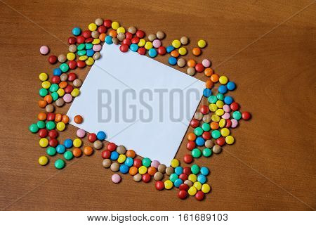 Candies and greeting card on wooden background. Top view with copy space
