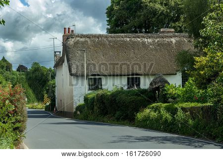 Typical Devonian house. White with a thatched roof. Devonshire. England