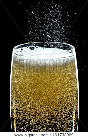 Close-up image of fizzing glass of champagne with dark background