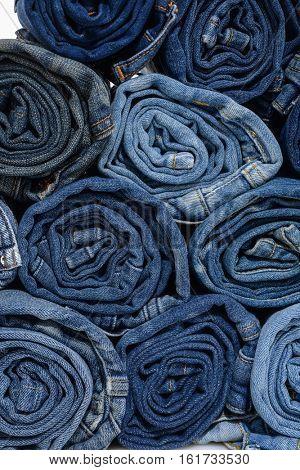 roll blue denim jeans arranged in stack