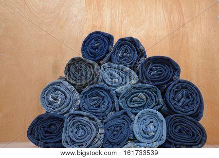 roll blue denim jeans arranged in stack-wooden background