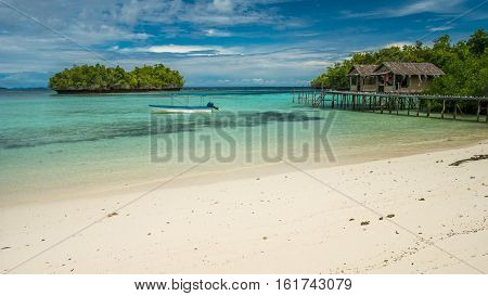 Beautiful Blue Lagoone with some Bamboo Huts, Kordiris Homestay, Palmtree in Front, Gam Island, West Papuan, Raja Ampat, Indonesia.