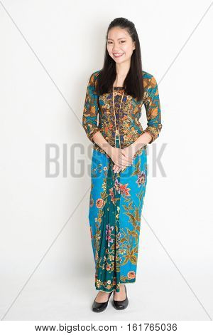Portrait of young southeast Asian girl in traditional Malay batik kebaya dress smiling, full length standing on plain background.